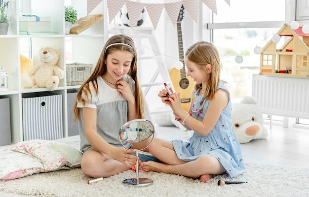 Glückliche kinder, die mit make-up-lippenstift im gemütlichen raum spielen