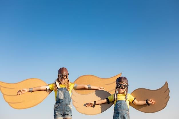 Glückliche kinder, die mit spielzeugflügeln gegen sommerhimmelhintergrund spielen. kinder haben spaß im freien.