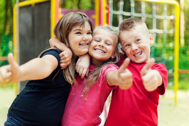 Glückliche kinder, die ok zeichen auf spielplatz zeigen