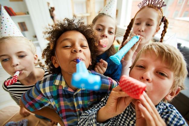 Glückliche kinder, die partyhörner blasen