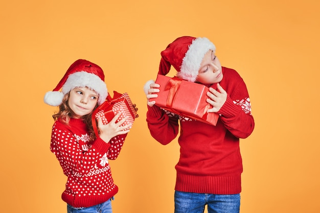 Glückliche kinder, die rote geschenkboxen halten
