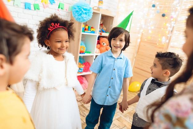Glückliche kinder, die runden tanz auf geburtstagsfeier tanzen.