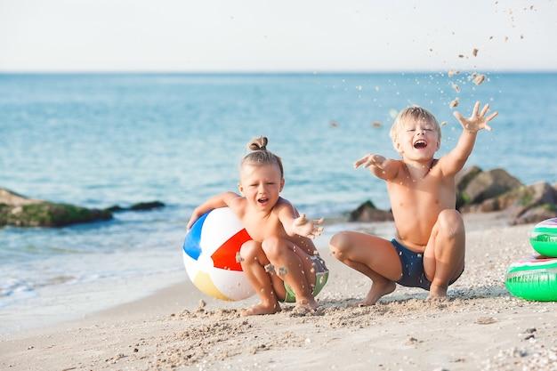 Glückliche kinder, die spaß am strand haben. aktive kinder auf sommerhintergrund.