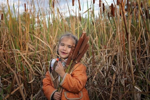 Glückliche kinder, die spaß auf dem gebiet von cattails, ökologiekonzept haben