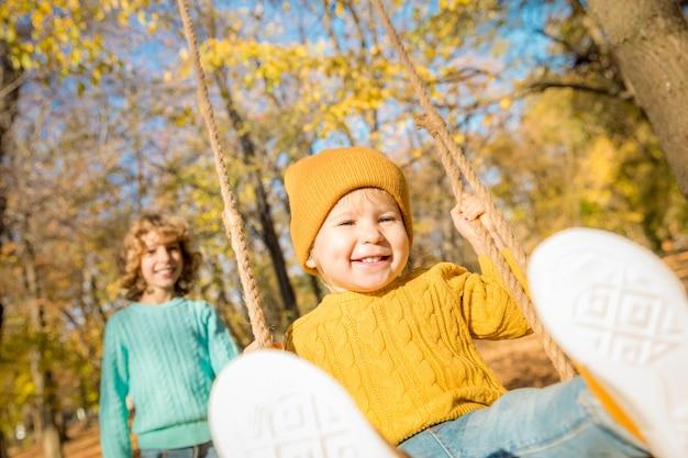 Glückliche kinder, die spaß draußen im herbstpark haben