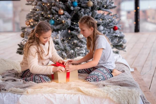 Glückliche kinder, die spaß haben und geschenke nahe weihnachtsbaum öffnen.