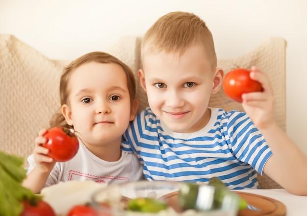 Glückliche kinder, die tomaten in den händen halten