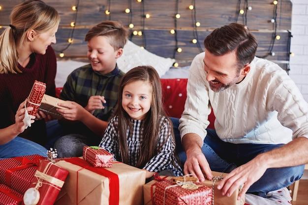 Glückliche kinder, die weihnachtsgeschenk mit eltern öffnen