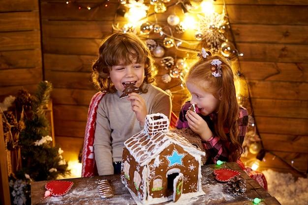 Glückliche kinder, die weihnachtslebkuchenhaus essen