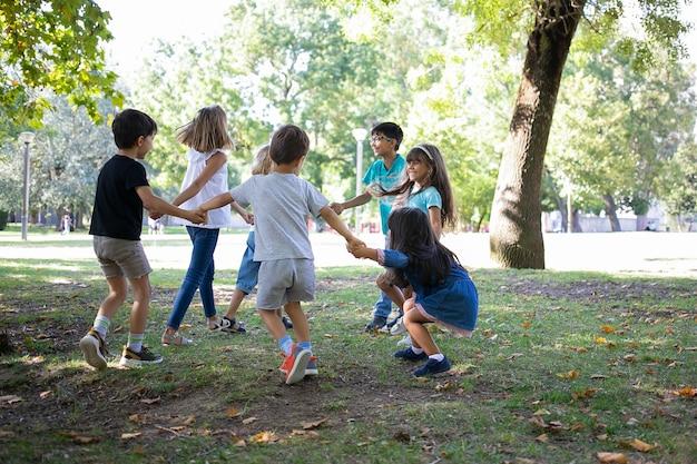 Glückliche kinder, die zusammen draußen spielen, auf gras tanzen, aktivitäten im freien genießen und spaß im park haben. kinderparty oder freundschaftskonzept
