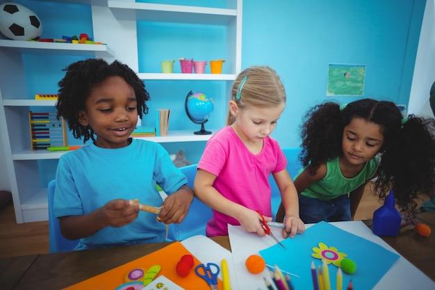 Glückliche kinder, die zusammen modellierlehm verwenden