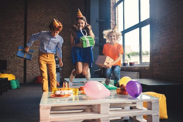 Glückliche kinder. drei freunde in bday hüten springen und sehen glücklich aus