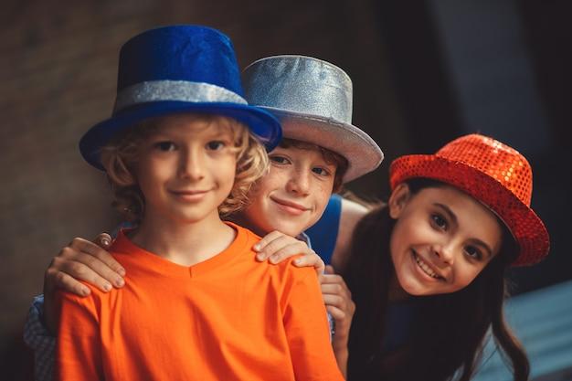 Glückliche kinder. drei freunde in partyhüten sehen glücklich aus