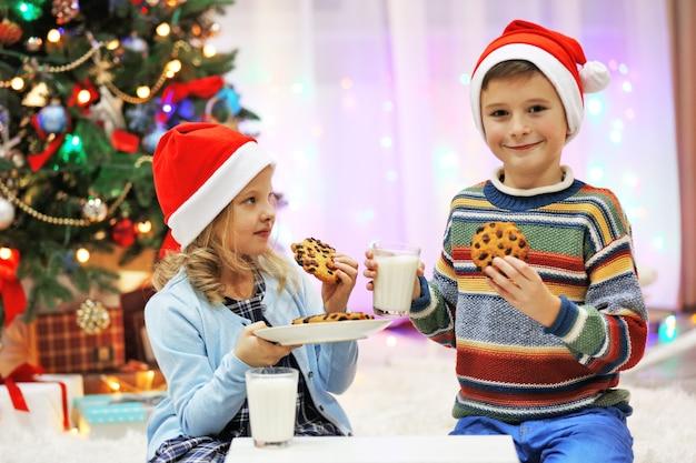 Glückliche kinder essen im dekorierten weihnachtsraum christmas