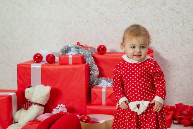 Glückliche kinder. feiern-konzept. nette babys mit einem roten geschenkkarton auf weißem hintergrund. nettes kleines kind halten geschenkbox.
