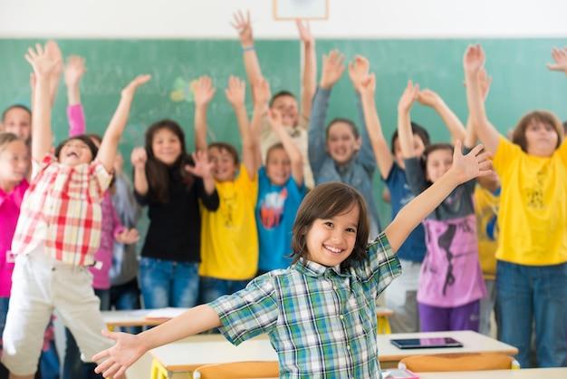Glückliche kinder gruppieren mit den armen, die im schulklassenzimmer ausgestreckt werden
