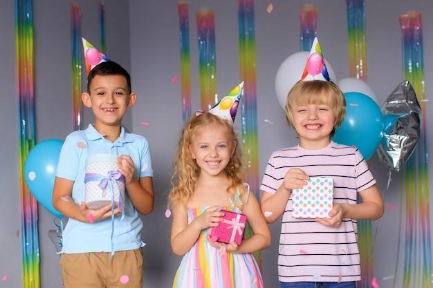 Glückliche kinder haben spaß in den ferien und springen in bunten konfetti