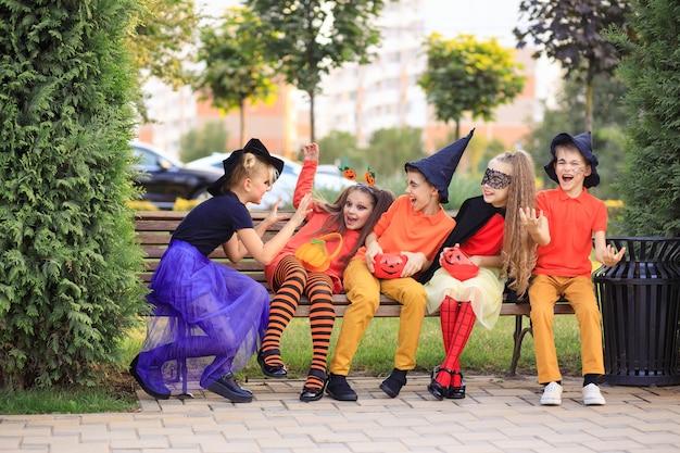 Glückliche kinder im park in den halloween-kostümen feiern die feiertage