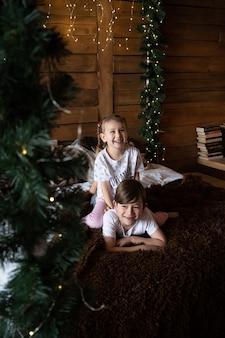 Glückliche kinder im pyjama, die am weihnachtsmorgen in der nähe des weihnachtsbaums spielen