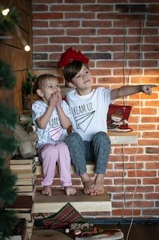 Glückliche kinder im pyjama, die mit dem finger nach oben zeigen, der über den kopierraum reicht. frohe weihnachten konzept neues jahr