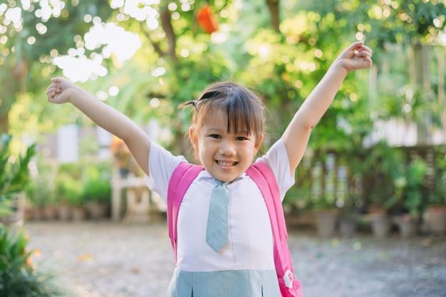 Glückliche kinder im studentenanzug und in der tasche bereit, zum lernen zur schule zu gehen