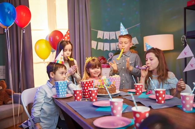 Glückliche kinder in den partykappen, die einen geburtstag feiern