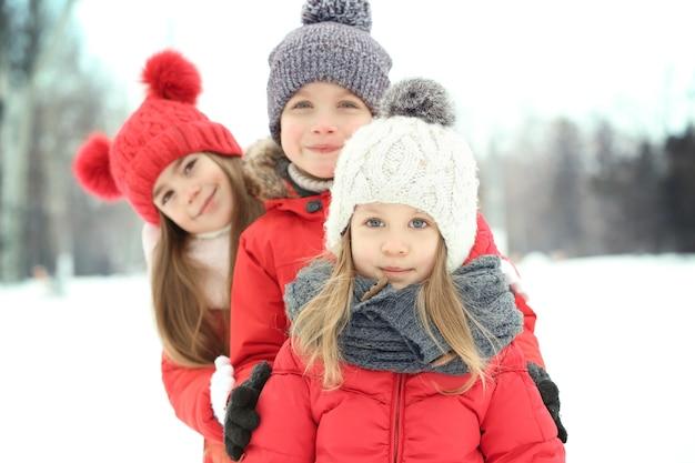Glückliche kinder in roter warmer kleidung, die im winter spaß im freien haben