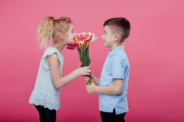 Glückliche kinder, junge streckt blumen zu einem kleinen mädchen im rosa kleid, lokalisiert auf blauer wand, seitenansicht