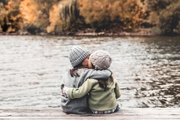 Glückliche kinder, kleine mädchen, sitzen und spielen auf einer holzbrücke. porträt. landschaftsorientierung.