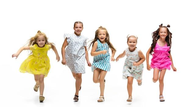 Glückliche kinder, kleine und emotionale kaukasische kinder, die isoliert auf weißem hintergrund springen und laufen. sieht glücklich, fröhlich, aufrichtig aus. exemplar für anzeige. kindheit, bildung, glückskonzept.