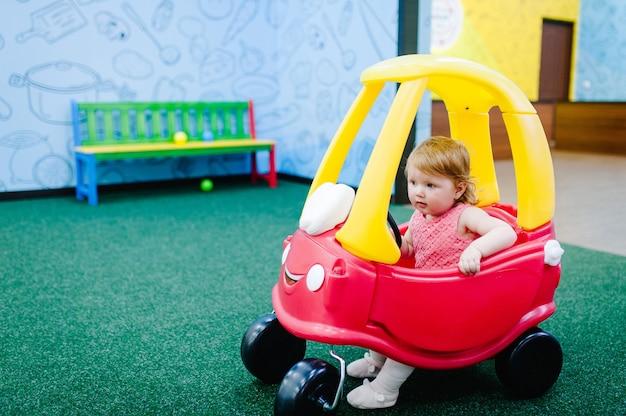 Glückliche kinder, kleines mädchen kind fährt auf einem roten großen auto auf der straße. das baby fährt auto und spielt auf einer geburtstagsfeier in einem kinderspielzimmer. zeit zusammen im unterhaltungszentrum.