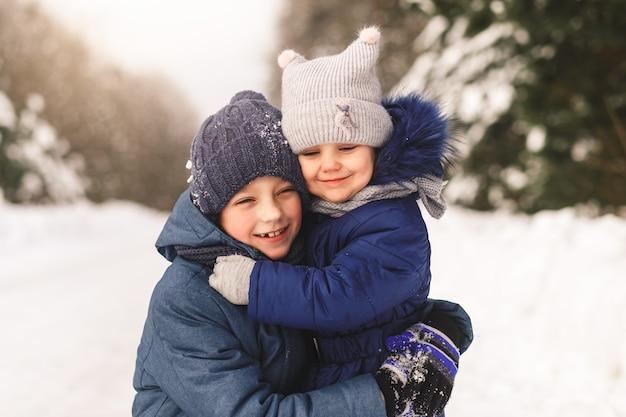 Glückliche kinder kuscheln im winter im wald. bruder und schwester zusammen
