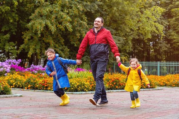 Glückliche kinder lachen, eilen und laufen in regenmänteln zur schule