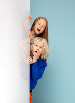 Glückliche kinder lokalisiert auf blauem studiohintergrund. sieht glücklich, fröhlich, aufrichtig aus. copyspace. konzept für kindheit, bildung, emotionen