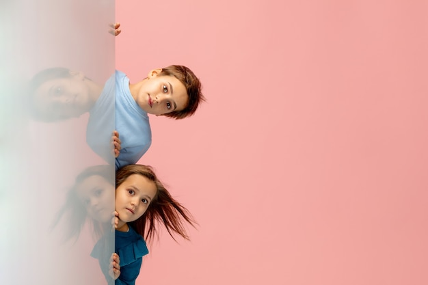 Glückliche kinder lokalisiert auf korallenrosa studiohintergrund. sieht glücklich, fröhlich, aufrichtig aus. copyspace. konzept für kindheit, bildung, emotionen