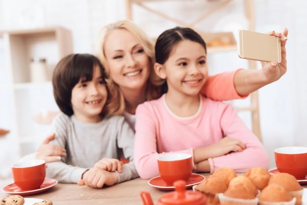 Glückliche kinder mit der großmutter, die selfie-küche macht