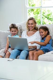 Glückliche kinder mit der mutter, die laptop auf sofa verwendet