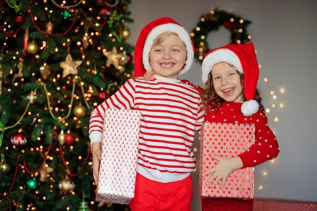 Glückliche kinder mit geschenken durch den weihnachtsbaum