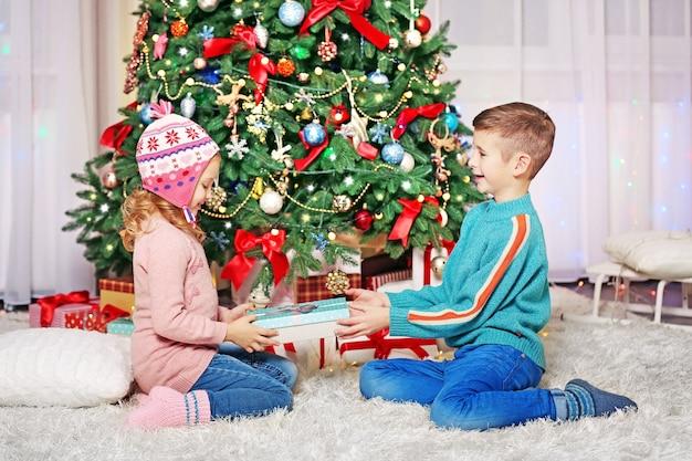Glückliche kinder mit geschenken im geschmückten weihnachtszimmer