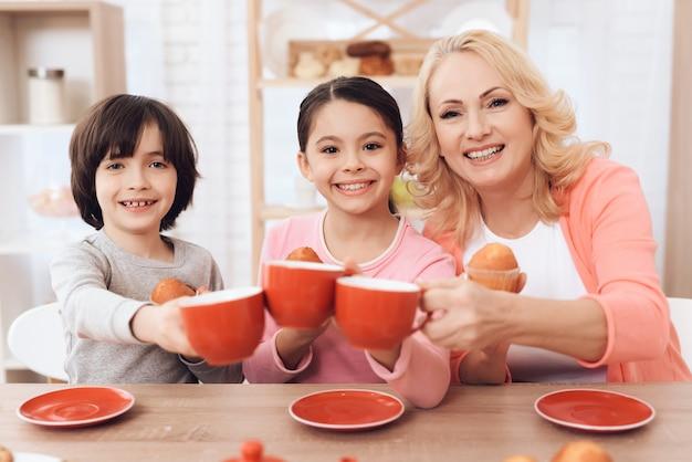 Glückliche kinder mit großmutter cheers cups mit tee