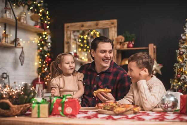 Glückliche kinder mit papa essen pizza in der küche für weihnachten dekoriert