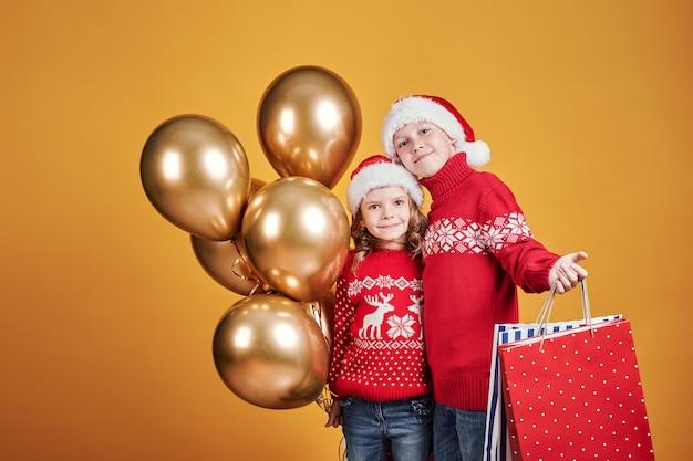 Glückliche kinder mit weihnachtsgeschenken und ballonen