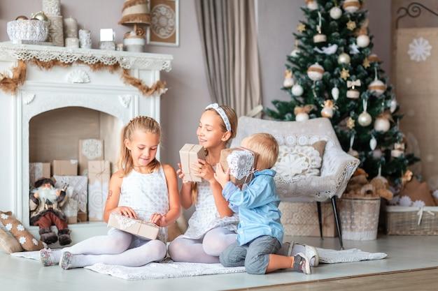 Glückliche kinder nahe weihnachtsbaum mit geschenken nahe kamin