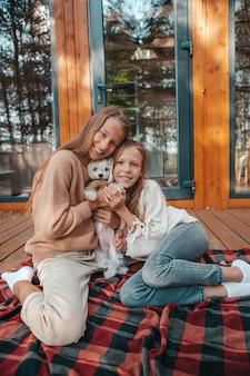 Glückliche kinder sitzen auf der terrasse ihres hauses im herbst