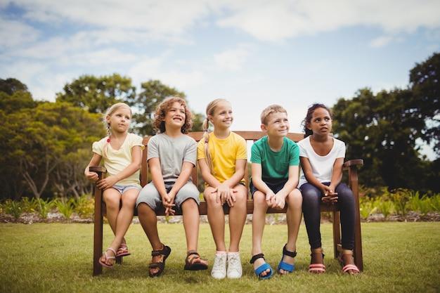 Glückliche kinder sitzen auf einer bank