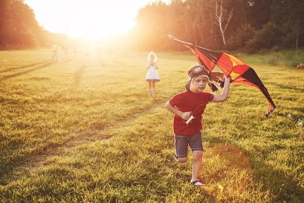 Glückliche kinder starten bei sonnenuntergang einen drachen auf dem feld. kleiner junge und mädchen in den sommerferien