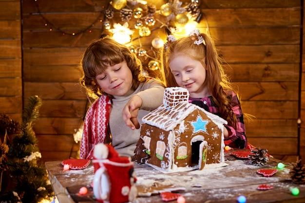 Glückliche kinder stellen weihnachtslebkuchen her.