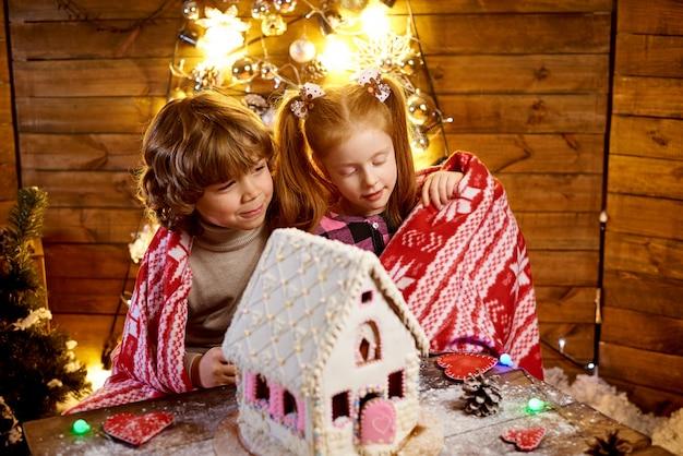 Glückliche kinder stellen weihnachtslebkuchenhaus her