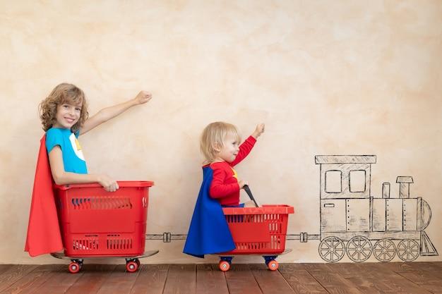 Glückliche kinder-superhelden, die zu hause spielen.