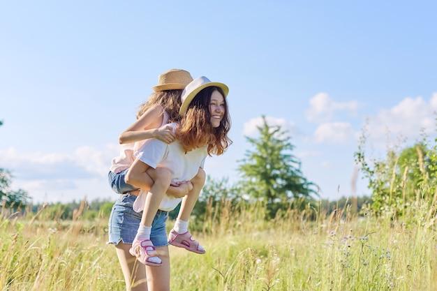 Glückliche kinder zwei mädchen schwestern teenager und jünger lachen und spaß auf der wiese, blauen himmel, sommernatur haben. aktiver gesunder lebensstil, freundliche familie, glückliche kindheit, kopierraum